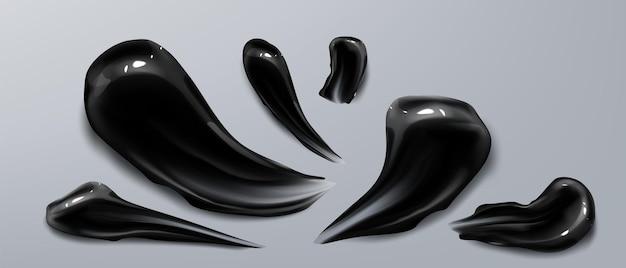 Schwarze holzkohlecreme verschmiert farbfelder von kohlenstoff-hautpflegekosmetika oder bambuszahnpasta, die auf realistischen flecken der grauen wand isoliert werden, satz von tonmasken-schönheitsprodukt für gesichts- oder körperpflege