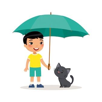 Schwarze miezekatze und netter kleiner asiatischer junge mit regenschirm.