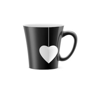 Schwarze tasse mit sich verjüngendem boden mit einem teebeutel in form eines herzens