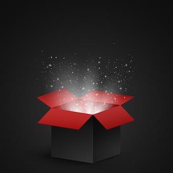 Schwarze und rote offene box mit magischem staub und leuchtend weißen partikeln auf dunklem hintergrund.