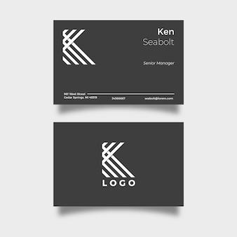 Schwarze visitenkarte mit weißem logobuchstaben