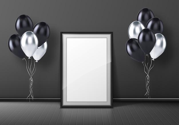 Schwarzer fotorahmen, der auf grauem hintergrund im leeren raum mit luftballons steht