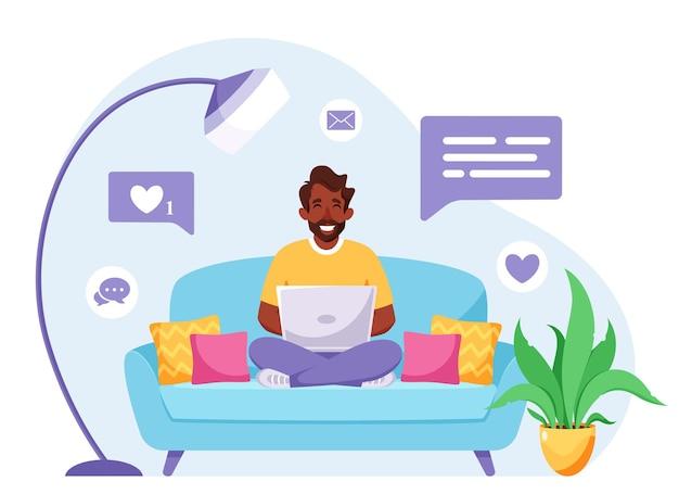 Schwarzer freiberufler sitzt auf einem sofa und arbeitet am laptop