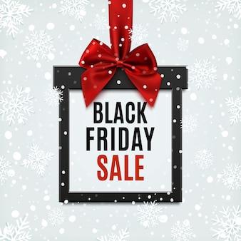 Schwarzer freitag-verkauf, quadratisches banner in form von weihnachtsgeschenk mit rotem band und bogen, auf winterhintergrund mit schnee und schneeflocken. broschüre oder banner vorlage.
