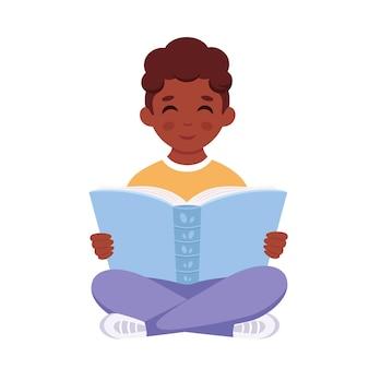 Schwarzer junge, der ein buch liest junge, der mit einem buch studiert