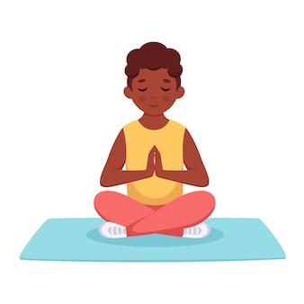 Schwarzer junge, der im lotussitz meditiert gymnastisches yoga und meditation für kinder