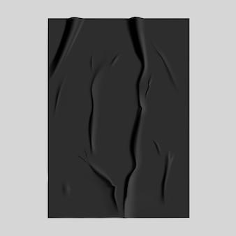 Schwarzes geklebtes papier mit nassem falteneffekt auf grauem hintergrund. schwarze nasse papierplakatschablone mit zerknitterter textur.