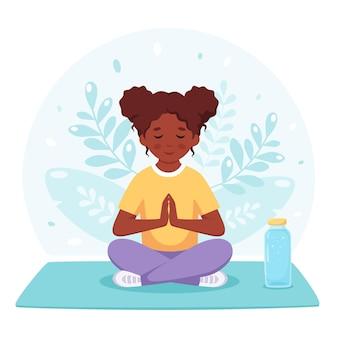 Schwarzes mädchen, das im lotussitz meditiert gymnastisches yoga und meditation für kinder