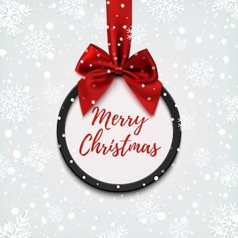 Schwarzes rundes banner der frohen weihnachten mit rotem band und schleife, lokalisiert auf weißem hintergrund. broschüre oder banner vorlage.