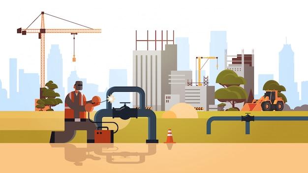 Schweißer in schutzmaske schweißen großer rohrstahlpipelines arbeiter in einheitlichem baukonzept baustellenhintergrund flach in voller länge horizontal
