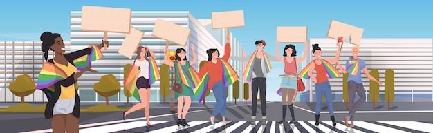 Schwule und lesben mit lgbt regenbogenfahnen halten protestplakate leere plakate lieben parade stolz festival demonstrationskonzept stadtbild hintergrund voller länge horizontal