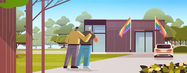 Schwules paar umarmt und betrachtet neues modulares haus mit regenbogenflaggen transgender-liebe lgbt-community