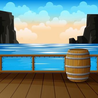 Seestückblick vom pier mit fass und felsen im wasser