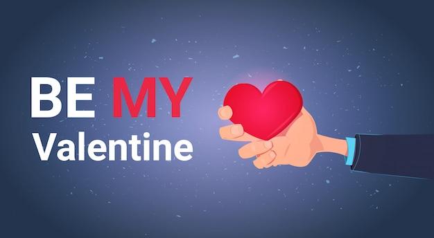 Seien sie meine valentine greeting card with hand, die rotes herz-liebes-feiertags-konzept hält