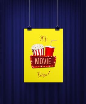 Sein filmzeitplakat mit popcorn-korb-cola-tasse und schild, das am blauen vorhang hängt