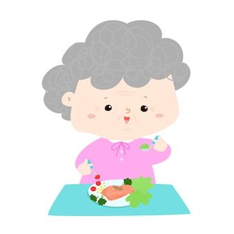 Senior, der gesunde lebensmittelkarikatur-vektorillustration isst großmutter, die auf dem tisch fischsteak und salat, leutelebensstilkonzept isst.