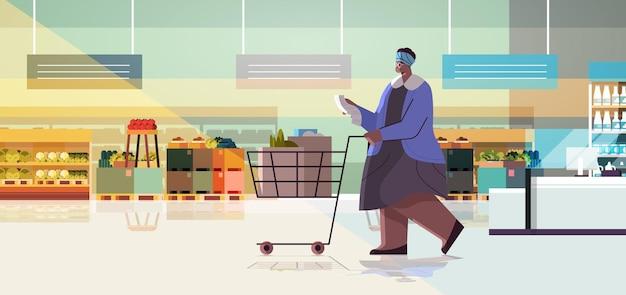 Senior frau mit voller produkte trolley warenkorb überprüfung der einkaufsliste im supermarkt modernes lebensmittelgeschäft innenraum horizontale vektorillustration in voller länge