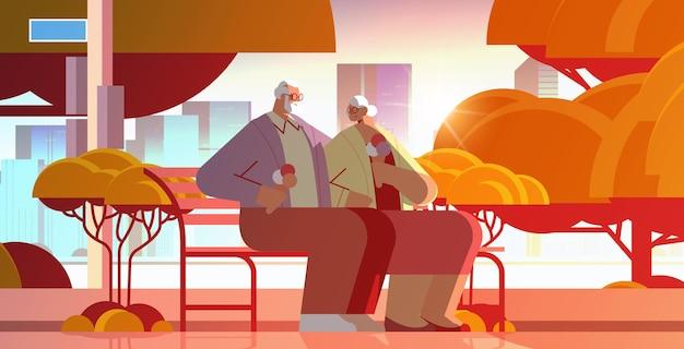 Senior paar sitzt auf der bank und isst eis glückliche großeltern verbringen zeit zusammen im park sonnenuntergang stadtbild hintergrund horizontale vektorillustration in voller länge