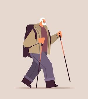 Senior wanderer, der mit rucksack und stöcken zum wandern nordic walking aktives alterskonzept reist