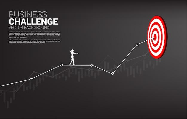 Silhouette der geschäftsfrau gehen seil auf linie grafik zur mitte der dartscheibe. targeting-konzept und business challenge. weg zum erfolg.