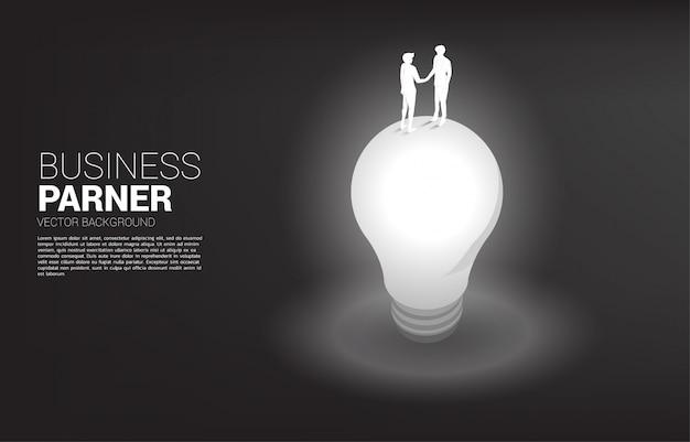Silhouette des geschäftsmann-handshake-oberteils der glühbirne. konzept der teamarbeit partnerschaft und zusammenarbeit.