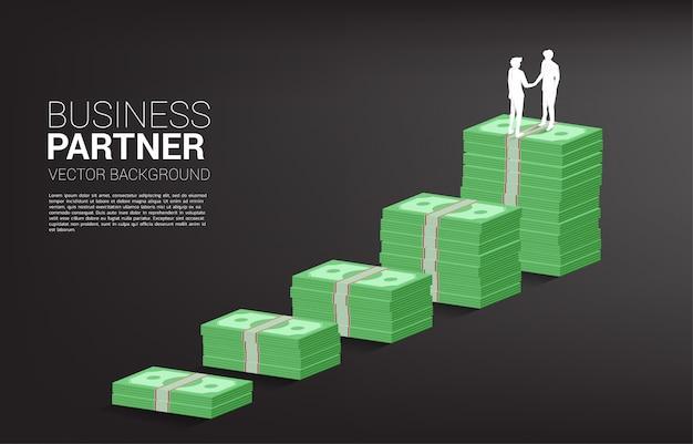 Silhouette des geschäftsmann-handshakes oben auf banknotengraph. konzept der geschäftspartnerschaft und zusammenarbeit.