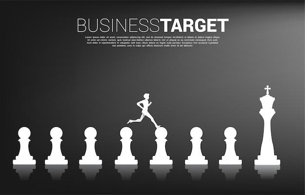 Silhouette des geschäftsmannes, der auf schachfigur vom bauern zum könig läuft. konzept von ziel, mission, vision, karriereweg und strategie