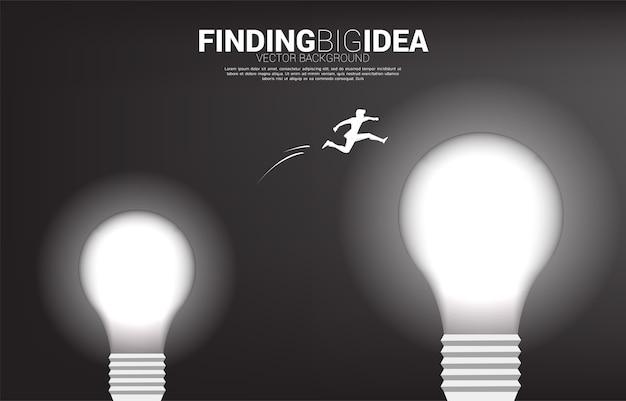 Silhouette des geschäftsmannes, der von der kleinen zur großen glühbirne springt. konzept für geschäftsrisiko für das finden der großen idee und des designdenkens