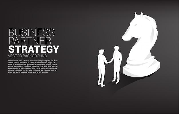 Silhouette des geschäftsmannhändedrucks mit schachfigurenritter. konzept der teamarbeit partnerschaft und kooperationsstrategie.