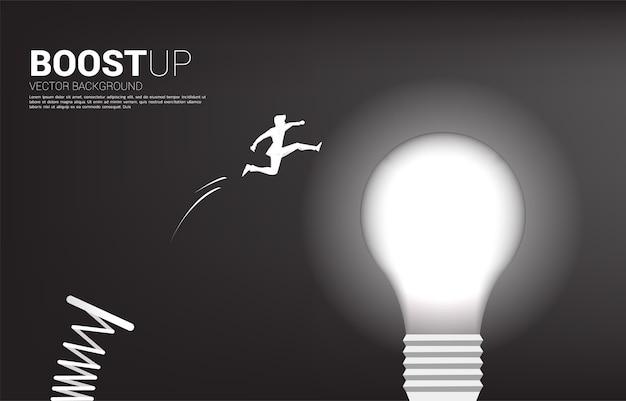 Silhouette des geschäftsmannsprungs zur glühbirne mit sprungbrett. geschäftskonzept der kreativen idee und lösung.