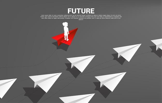 Silhouette des mädchens, das auf rotem origami-papierflugzeug steht, gehen anderen weg als gruppe von weiß