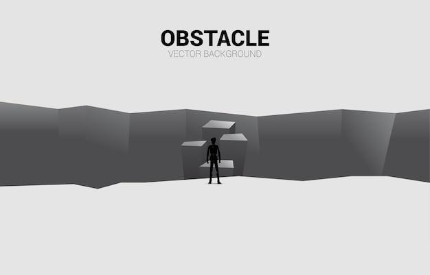 Silhouette eines geschäftsmannes, der auf schritt vorwärts zum abgrund steht.