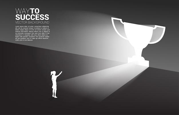 Silhouette geschäftsfrau, die im licht von ausgangstürformtrophäe steht. geschäftskonzept der route zum gewinner und champion