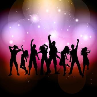 Silhouetten von menschen unter bunten lichtern tanzen