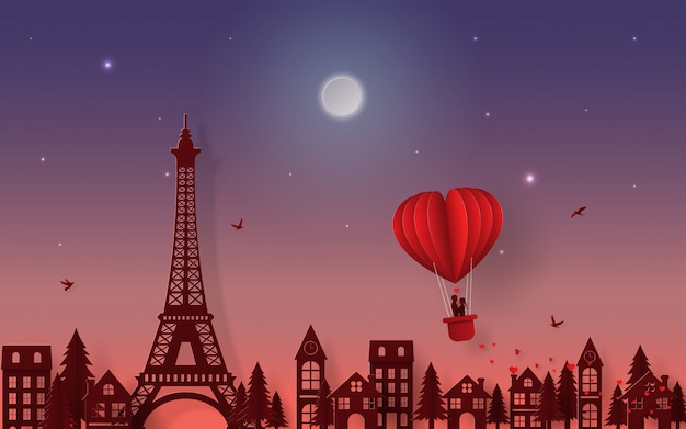 Silhouettieren sie paare auf dem ballon, der über paris-stadt schwimmt