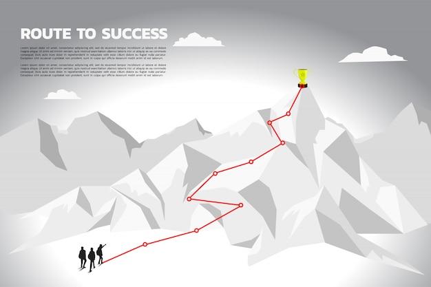 Silhouettieren sie teamgeschäftsmannplan, um meistertrophäe auf berg zu erhalten.