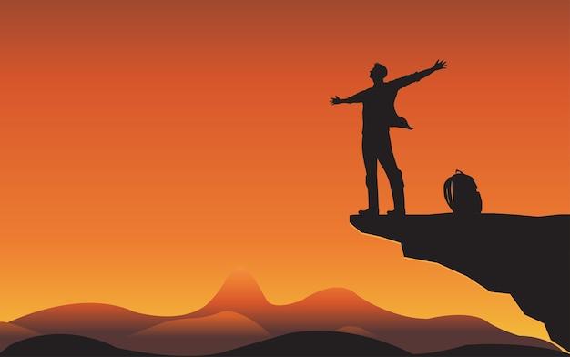 Sillhouette-mann auf bergklippe