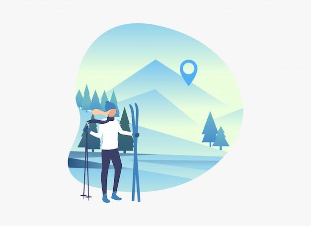 Skifahrerfrau, die skis und pfosten mit schneebedeckter landschaft hält