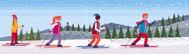 Skifahrergruppe, die den berg schiebt