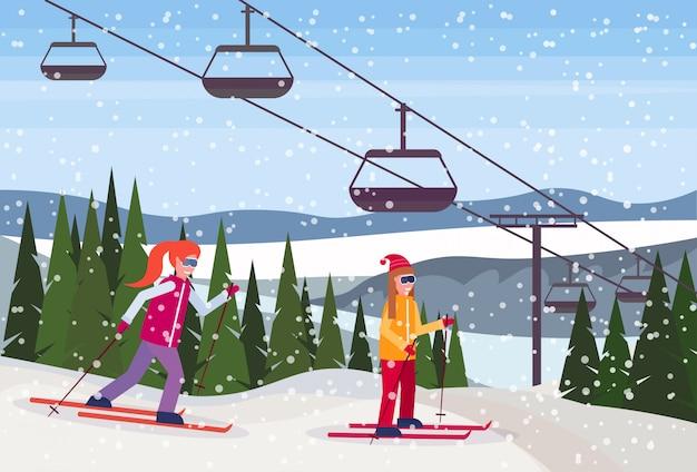 Skifahrerinnen rutschen den berg hinunter