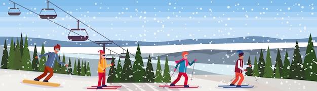 Snowboarder und skifahrer rutschen den berg hinunter