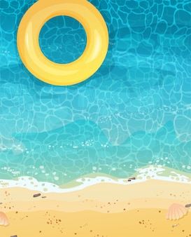 Sommerküste mit sand und gelbem schwimmring, draufsicht. die welle rollt auf sand, meerschaum und blaues wasser.