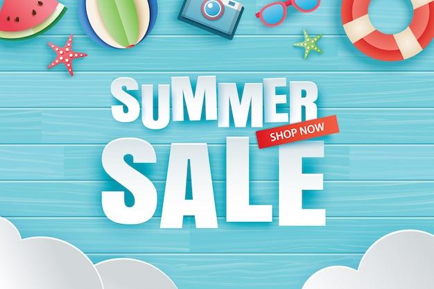 Sommerverkauf mit dekorationsorigami auf blauem hölzernem hintergrund.