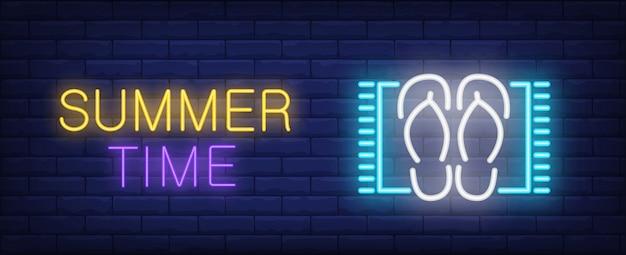 Sommerzeit neon stil schriftzug. flipflops auf strandmatte auf ziegelsteinhintergrund.