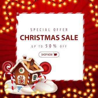 Sonderangebot, weihnachtsverkauf, bis zu 50 rabatt. rabattbanner des roten quadrats mit weihnachtsgirlande, weißem papierblatt und weihnachtslebkuchenhaus