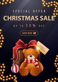 Sonderangebot, weihnachtsverkauf, bis zu 50% rabatt, wunderschönes dunkelblaues rabatt-banner mit goldenen buchstaben und geschenk mit teddybär