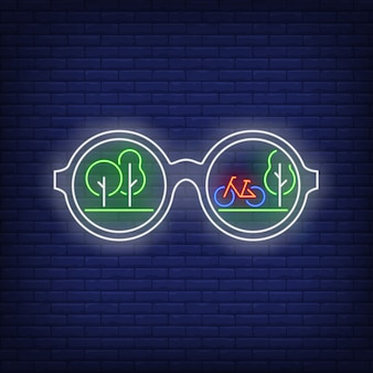 Sonnenbrille mit grünen bäumen und fahrradreflexionsleuchtreklame