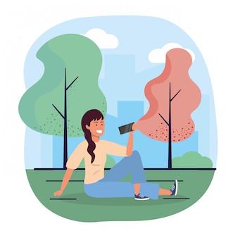Spaßfrauensitzplätze mit smartphone und bäumen