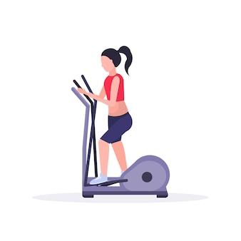 Sportfrau, die cardio-übungsmädchen unter verwendung von sportmaschinen-trainingsgeräten ausführt, die im fitnessstudio crossfit-training des gesunden lebensstilkonzepts weißen hintergrund horizontal trainieren
