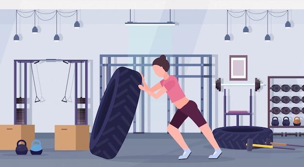 Sportfrau, die einen reifen umdreht, der harte übungsmädchen tut, das im crossfit-training des gesunden fitness-lifestyle-konzepts des modernen gesundheitsclubs studio interieur horizontal trainiert